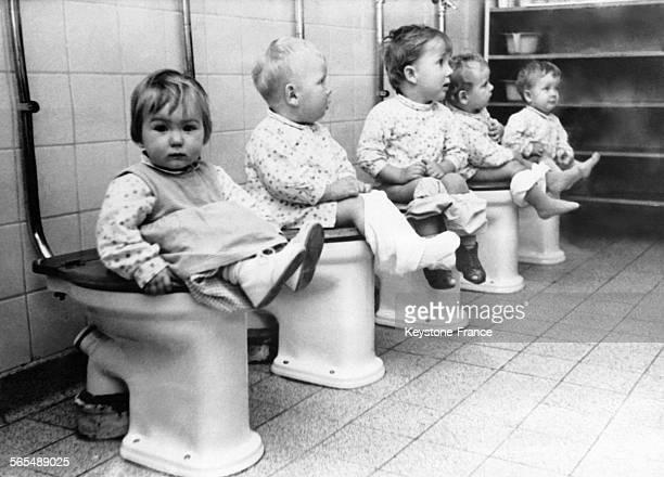 Des élèves d'une école maternelle sur la cuvette des WC pendant la récréation dans une écolepilote le 21 octobre 1964 en France