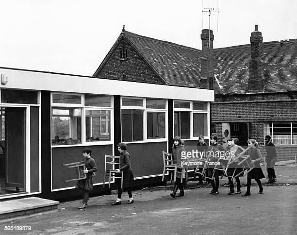 Des élèves d'une école primaire déménagent les chaises de leur classe vers le nouveau bâtiment le 13 janvier 1966 à Coventry RoyaumeUni
