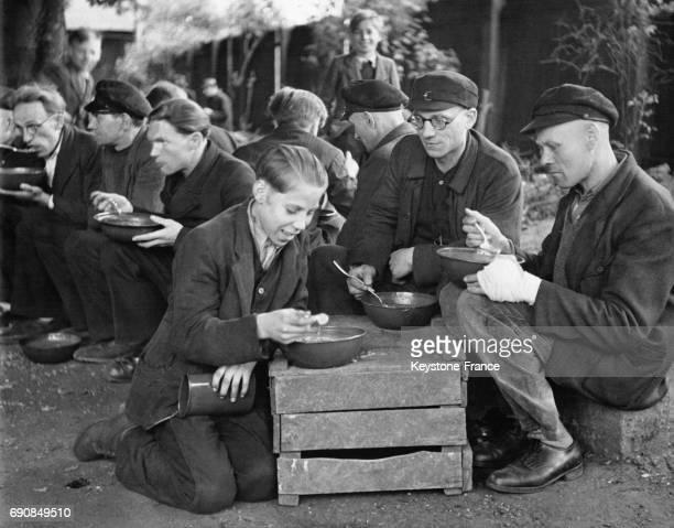 Des mineurs et ouvriers photographiés pendant leur pause déjeuner en plein air durant laquelle ils mangent leur soupe unique repas de la journée en...