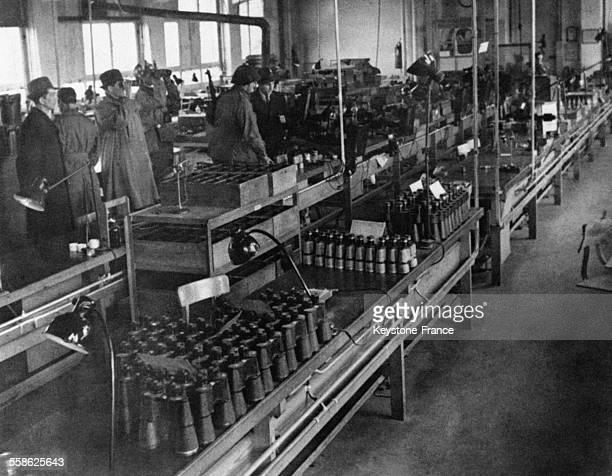 Des officiers américains visitant une partie intacte de l'usine Leica la plus grande du monde capturée par l'armée américaine leur guide en manteau...