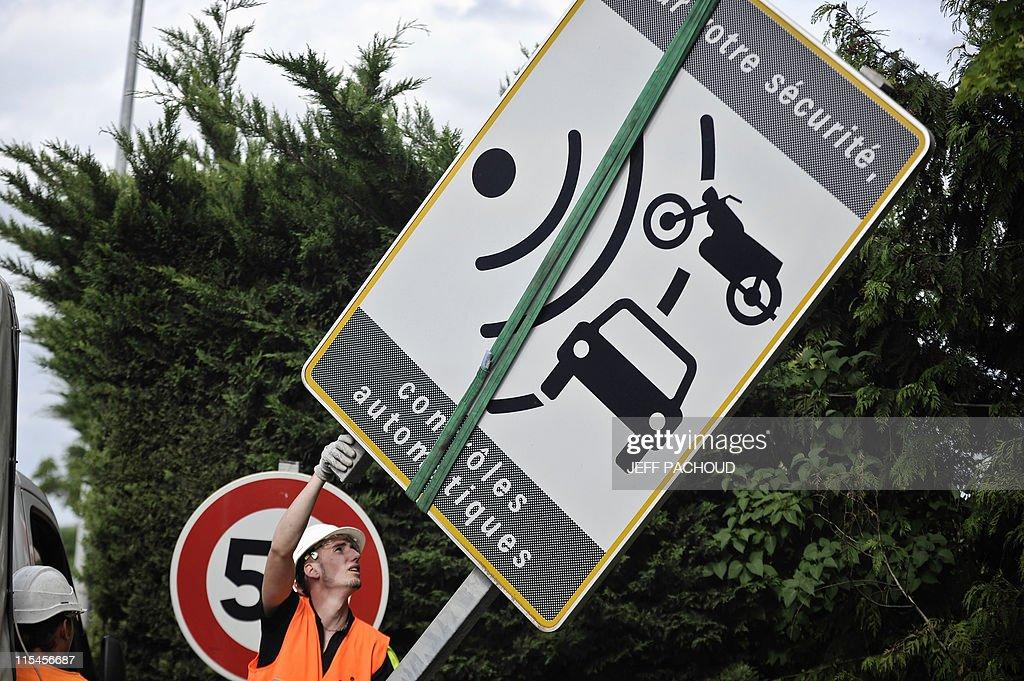 Des ouvriers de la société de services Spie démontent un panneau avertissant de la présence d'un radar, le 16 mai 2011 à Dijon, à la suite d'une des mesures du gouvernement destinée à enrayer la remontée du nombre de morts sur les routes. Une majorité de Français (65%) se déclarent contre la suppression des panneaux prévenant de la présence de radars automatiques, selon un sondage réalisé par l'Institut Harris Interactive pour le site autoplus.fr. AFP PHOTO / JEFF PACHOUD