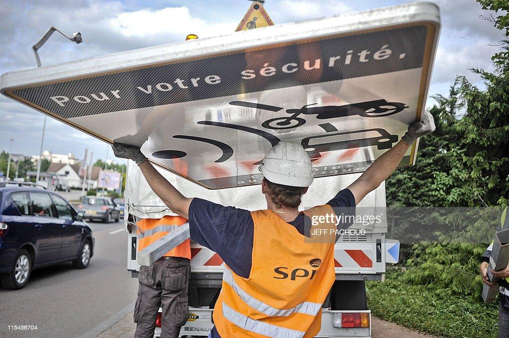 Des ouvriers de la société de services Spie démontent un panneau avertissant de la présence d'un radar, le 16 mai 2011 à Dijon, à la suite d'une des mesures du gouvernement destinée à enrayer la remontée du nombre de morts sur les routes. Une majorité de Français (65%) se déclarent contre la suppression des panneaux prévenant de la présence de radars automatiques, selon un sondage réalisé par l'Institut Harris Interactive pour le site autoplus.fr.