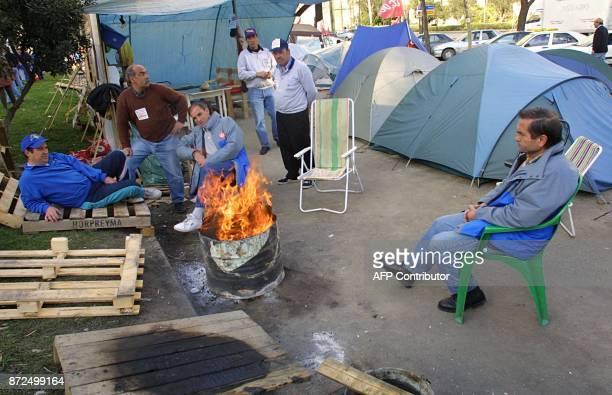 Des ouvriers en grève de l'entreprise espagnole de télécommunications Sintel se réchauffent près d'un feu le 13 février 2001 sur l'avenue Castellana...