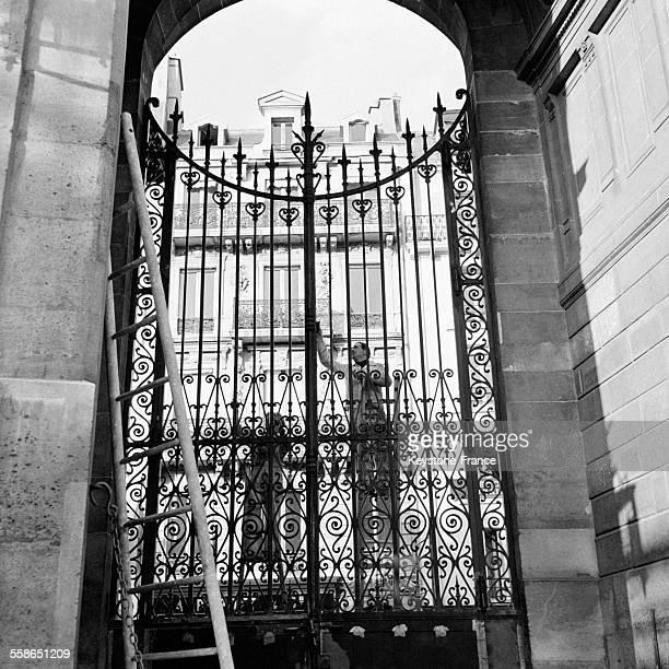 Des ouvriers peignent les grilles d'entrée du palais de l'Elysée à Paris France le 23 septembre 1954