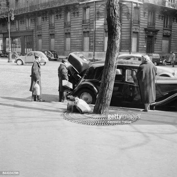 Des Parisiens sur le départ remplissent le coffre de leur voiture à Paris France le 29 mars 1956