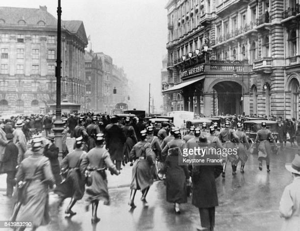 Des policiers municipaux accourent pour dégager la voie à la voiture ramenant Adolf Hitler après son entrevue avec Hindenburg à l'hôtel Kaiserhof où...