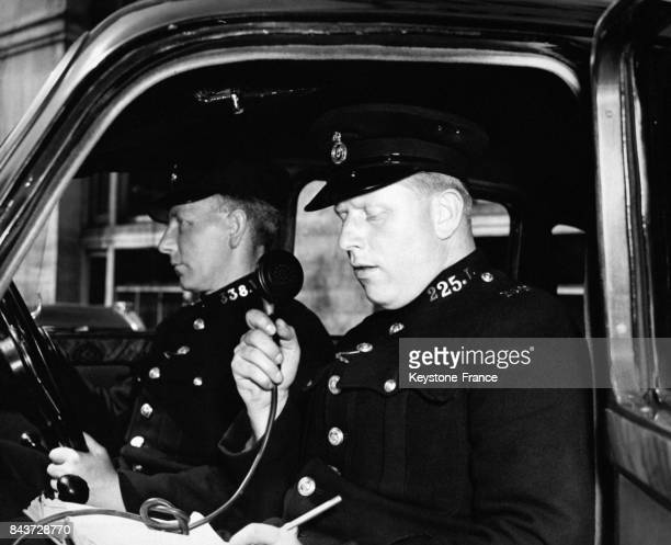 Des policiers patrouillant en voiture reçoivent un appel urgent de Scotland Yard à Londres RoyaumeUni circa 1930