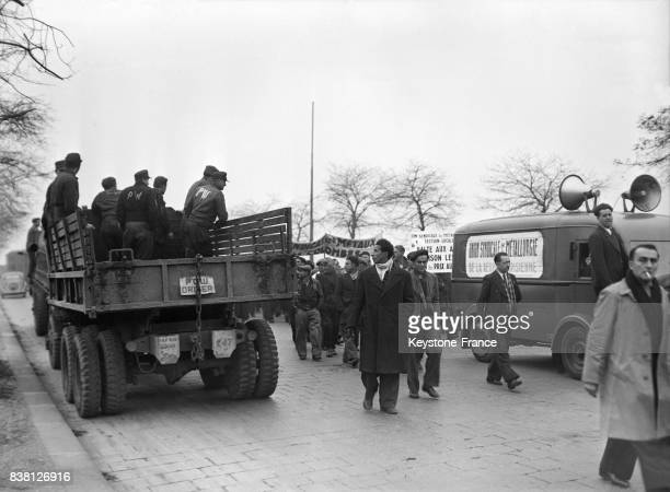 Des prisonniers allemands dans un camion américain regardent les manifestants protestant contre l'insuffisance et la cherté de la viande devant les...