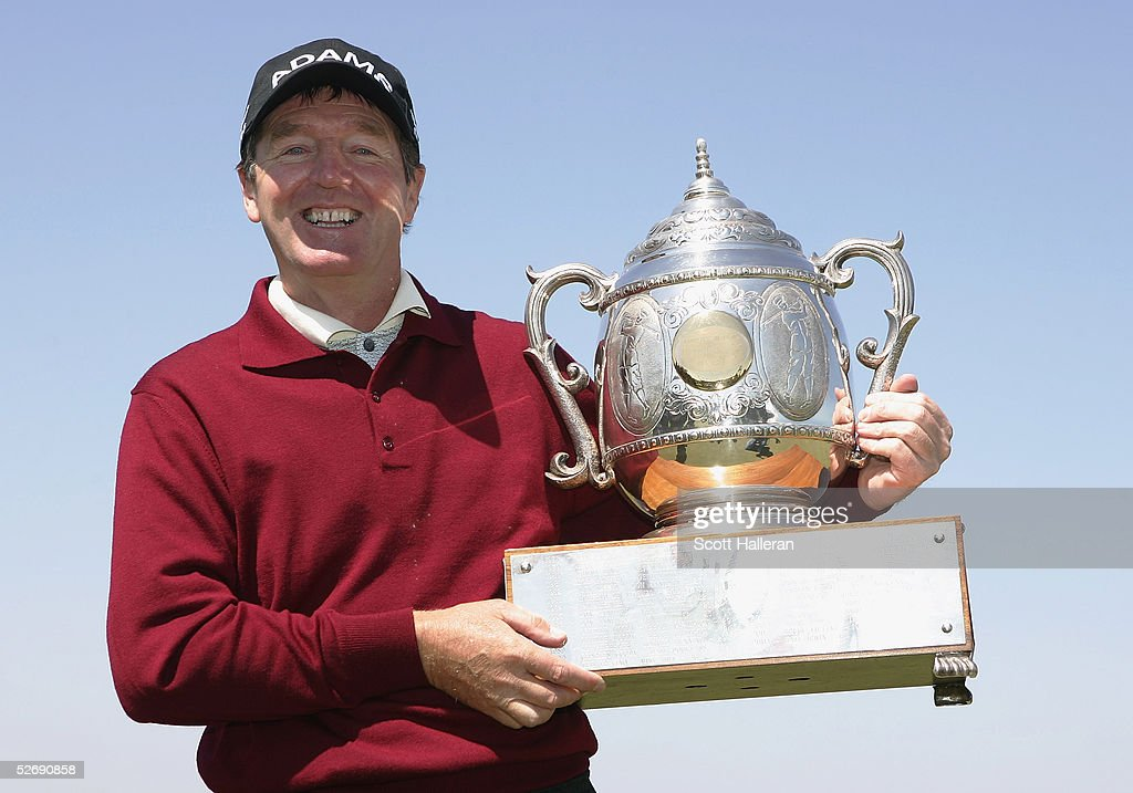 Des Smyth of Ireland poses with the trophy on the 18th green after a twostroke victory during the final round of the Liberty Mutual Legends of Golf...