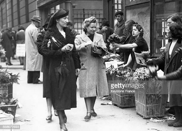 Des vendeuses de muguet proposent des bouquets aux passantes près de la Gare SaintLazare le 1er mai 1940 à Paris France