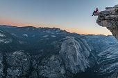 Aventurero sentado en la cumbre de la cima Half Dome en California. A sus pies el precipicio y las maravillosas vistas le acompañan.