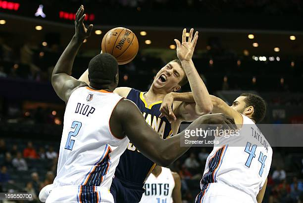DeSagana Diop of the Charlotte Bobcats and teammate Jeffery Taylor try to stop Tyler Hansbrough of the Indiana Pacers during their game at Time...