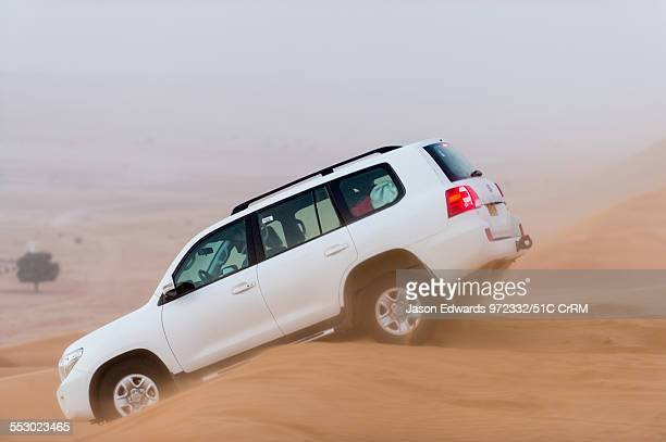 A 4WD descends a dune during a sand storm Wahiba Sands Ramlat alWahiba Sharqiya Sands Sultanate of Oman