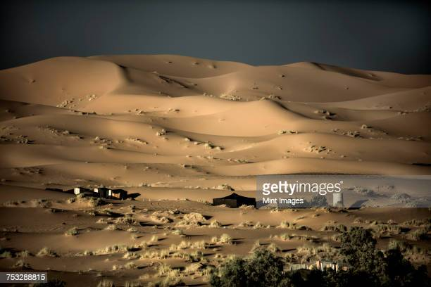 Desert landscape with sand dunes, tents in the middle distance.