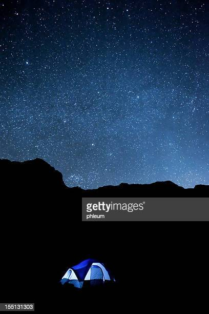 Desert night sky with camping tent and silhouetted cliffs