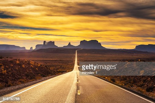 Desert road leading to Monument Valley at sunset : Foto stock