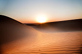 Sun setting over a horizon with sand dunes in the desert at dusk.