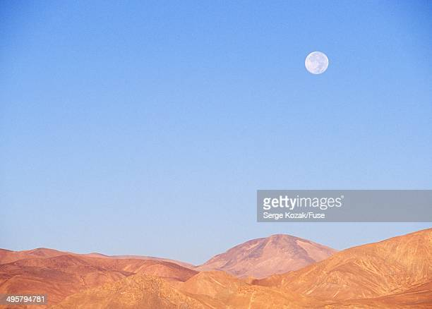 Desert wilderness landscape with full moon low on horizon, Tibet, China