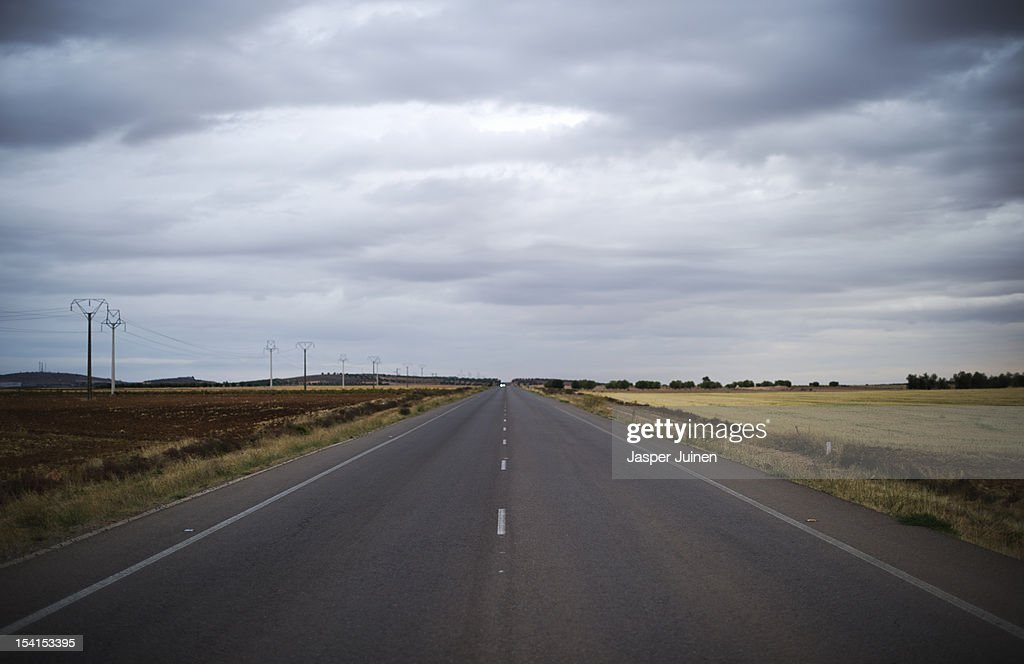 A deserted road stretches through the windswept La Mancha countryside on October 11, 2012 in the direction of the small industrial town of Villacanas, Spain. During the boom years, where in its peak Spain built some 800,000 houses a year, more than Britain, Germany and France combined, and millions of wooden doors where needed, the people of Villacanas were part of a proud elite enjoying high wages and permanent jobs. Almost all of those doors used came from this small industrial town in the La Mancha province, some seven million a year, leaving with truck loads at the same time, from the now empty and silent Villacanas industrial park. With Spain in recession and the housing bubble busted, the door industry is shattered and unemployment in Villacanas, zero for nearly a generation, is rising fast.