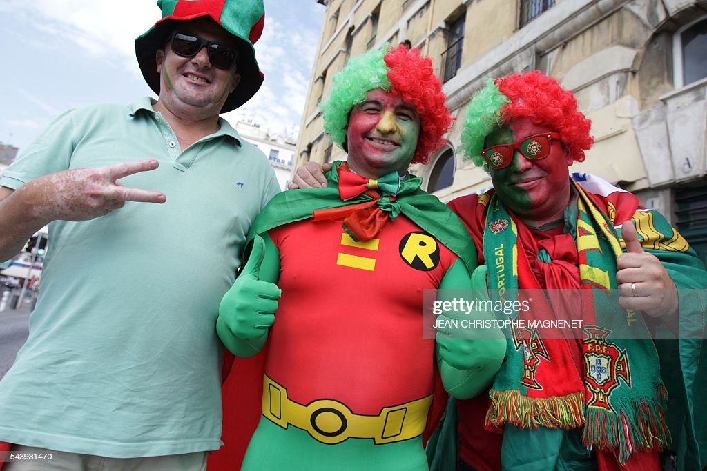 Desguised Portugal supporters gesture as they cheer ahead of the Euro 2016 championship match between Poland and Portugal, in Marseille, southern France, on June 30, 2016. / AFP / JEAN