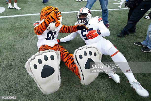Deshaun Davis of the Auburn Tigers celebrates with the team mascot after winning the Birmingham Bowl against the Memphis Tigers at Legion Field on...