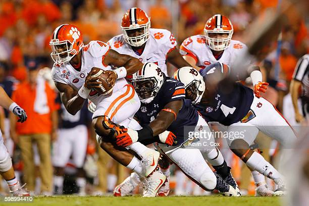 Deshaun Watson of the Clemson Tigers carries the ball against Montravius Adams and Jeff Holland of the Auburn Tigers during the first half at Jordan...