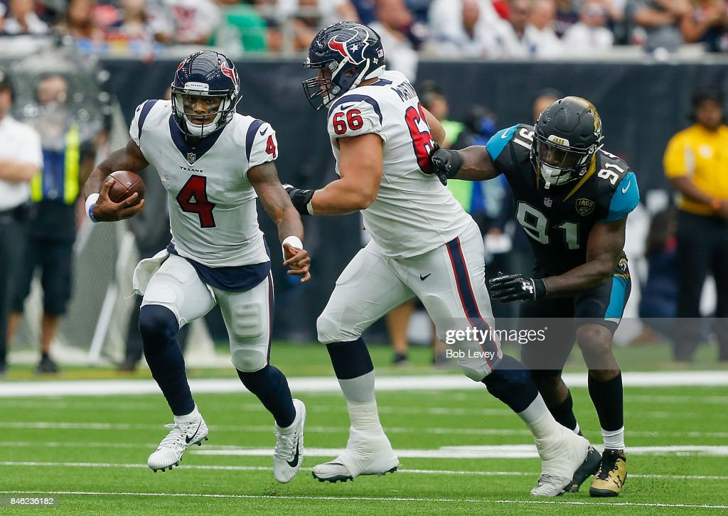 Deshaun Watson #4 of the Houston Texans runs out of the pocket as Nick Martin #66 attempts to keep Yannick Ngakoue #91 of the Jacksonville Jaguars from tackling him at NRG Stadium on September 10, 2017 in Houston, Texas.