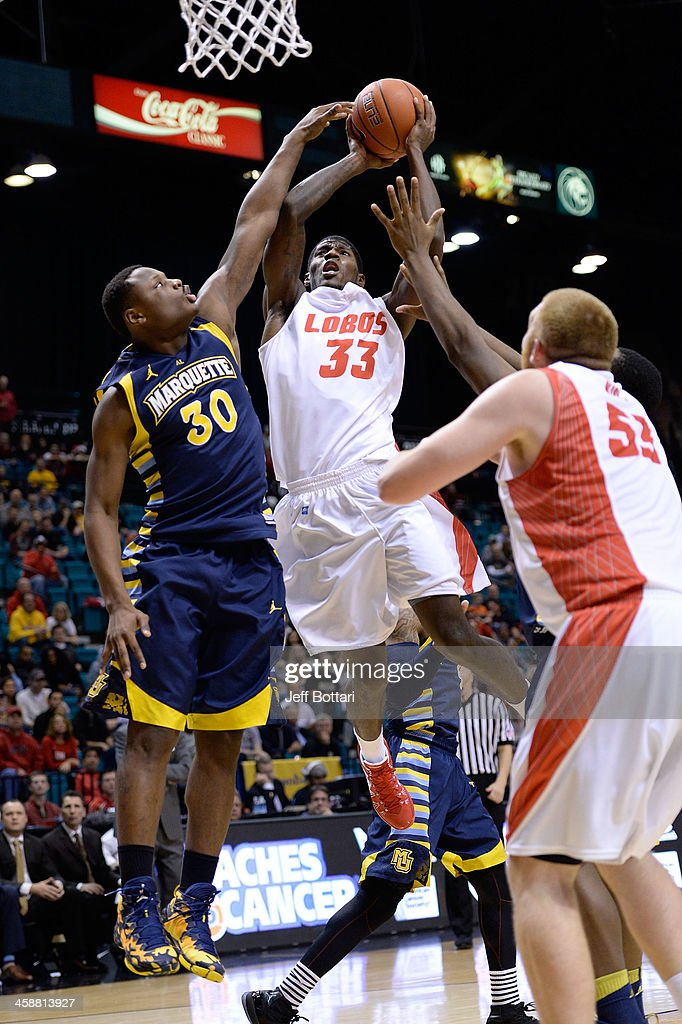 Deshawn Delaney #33 of the New Mexico Lobos drives to the basket against <a gi-track='captionPersonalityLinkClicked' href=/galleries/search?phrase=Deonte+Burton+-+Basketball+Player+-+Born+1994&family=editorial&specificpeople=15541085 ng-click='$event.stopPropagation()'>Deonte Burton</a> #30 of the Marquette Golden Eagles during their game at the MGM Grand Garden Arena on December 21, 2013 in Las Vegas, Nevada. New Mexico won 75-68.