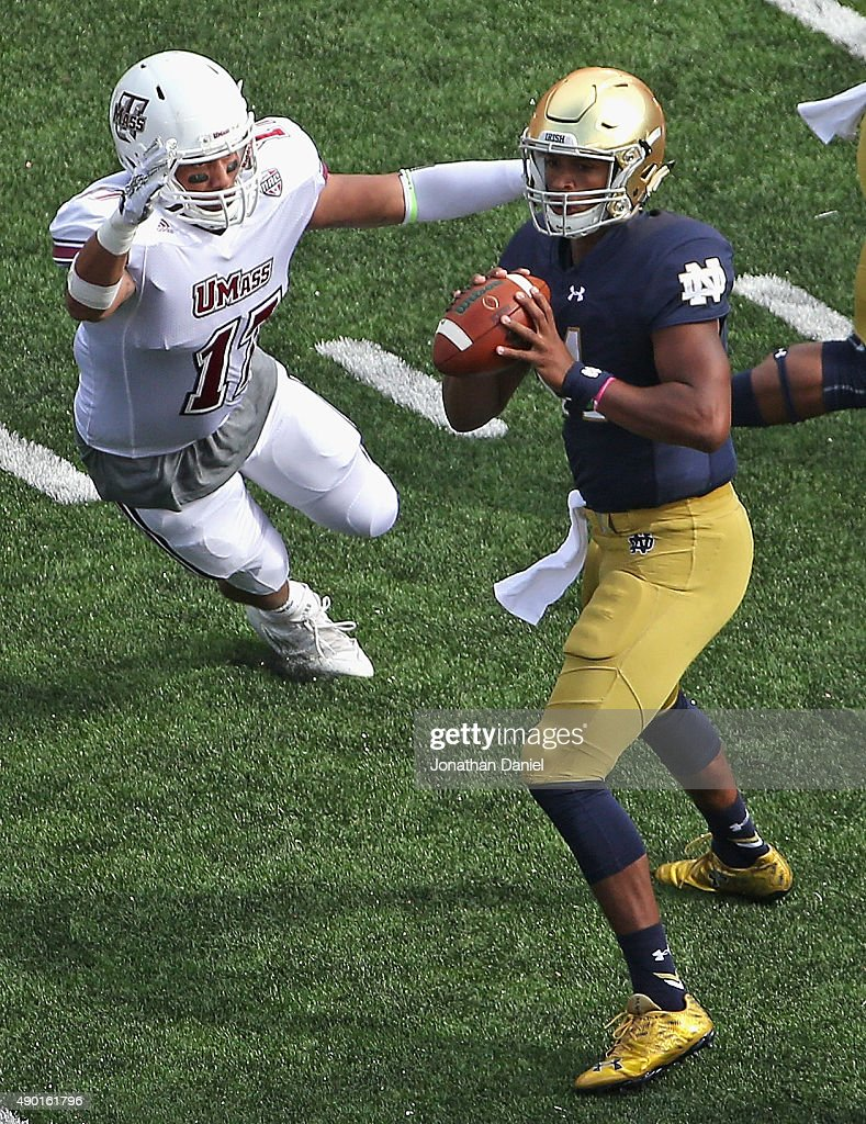 DeShone Kizer of the Notre Dame Fighting Irish looks to pass under pressure from Jovan SantosKnox of the Massachusetts Minutemen at Notre Dame...