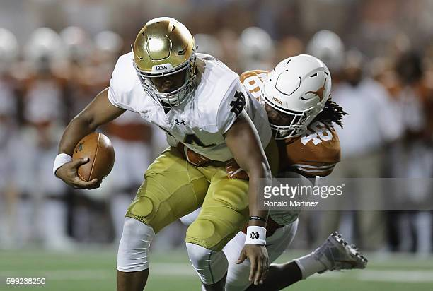 DeShone Kizer of the Notre Dame Fighting Irish runs with the ball as Malik Jefferson of the Texas Longhorns attempts to tackle him during the second...