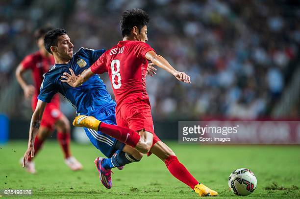 Deshuai Xu of Hong Kong competes for the ball with Leonel Vangioni of Argentina during the HKFA Centennial Celebration Match between Hong Kong and...