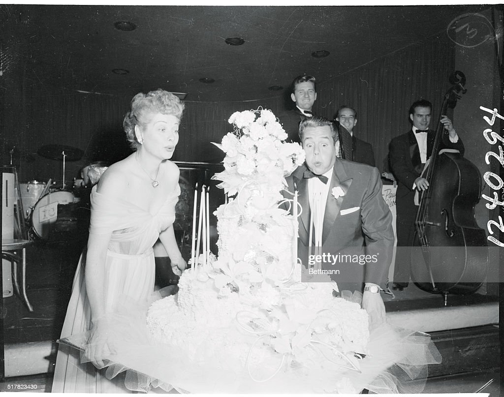 desi-arnaz-and-lucille-ball-blow-out-candles-on-their-13th-wedding-picture-id517823430