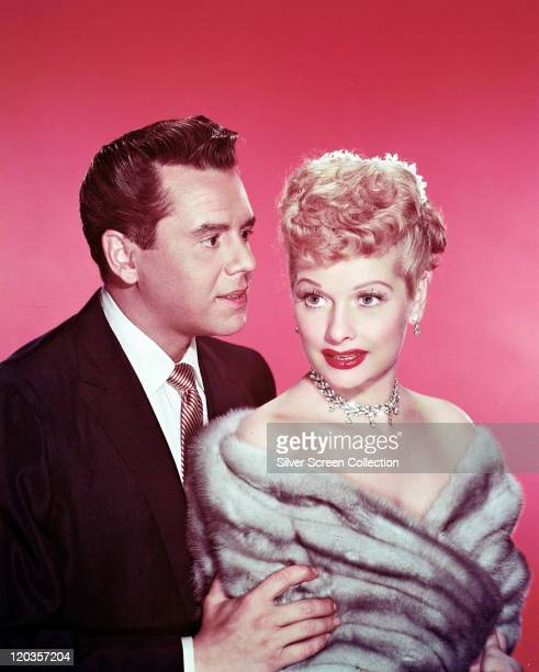 Desi Arnaz Cuban musician and actor with Lucille Ball US comedian and actress wearing a grey fur stole in a studio portrait against a red background...