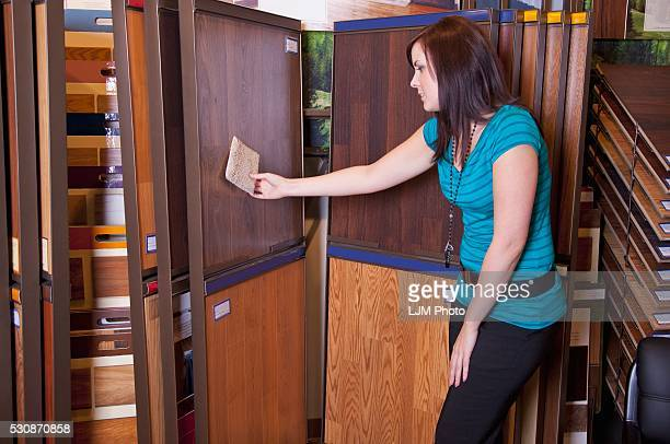 Design Consultant Compares Samples In A Retail Flooring Store; Edmonton, Alberta, Canada