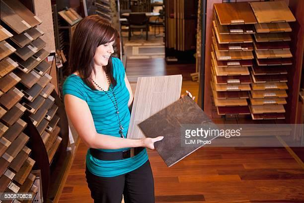 Design Consultant Showing Samples In A Retail Flooring Store; Edmonton, Alberta, Canada