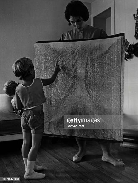 Design in Water Paint Stephanie looks at a 'Flood Picture' held by her mother Mrs SG Seay of 3406 W Powers Place Littleton It's a home movie screen...