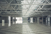 Interior of grey big empty warehouse complex with pendant lamps