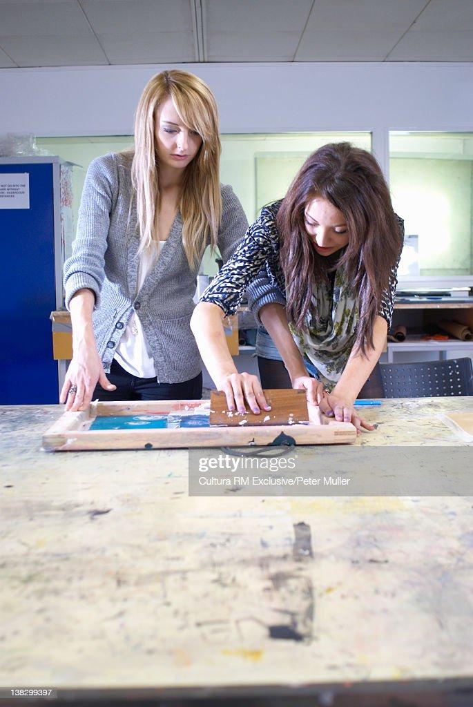 Design students screen printing on fabric : Stock Photo