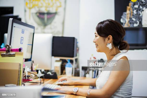 Design Studio. A woman sitting at a desk using a computer.