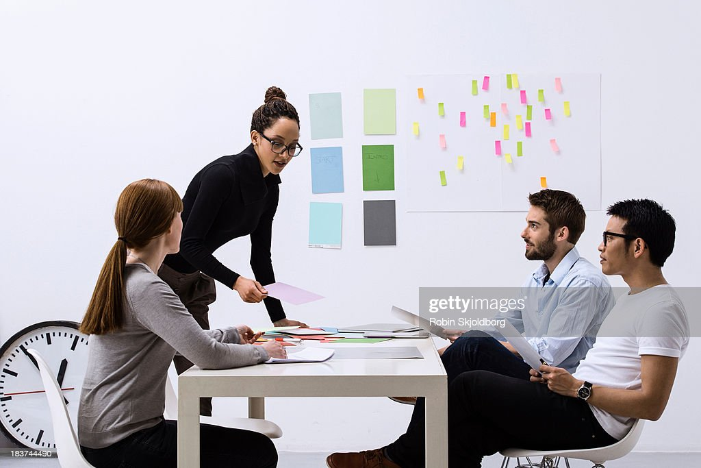 Design team sitting at table discussing ideas : Stock Photo