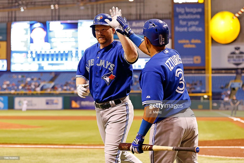 Designated hitter <a gi-track='captionPersonalityLinkClicked' href=/galleries/search?phrase=Adam+Lind&family=editorial&specificpeople=3911783 ng-click='$event.stopPropagation()'>Adam Lind</a> #26 of the Toronto Blue Jays is congratulated by <a gi-track='captionPersonalityLinkClicked' href=/galleries/search?phrase=Maicer+Izturis&family=editorial&specificpeople=239100 ng-click='$event.stopPropagation()'>Maicer Izturis</a> #3 after his second inning home run against the Tampa Bay Rays at Tropicana Field on May 7, 2013 in St. Petersburg, Florida.