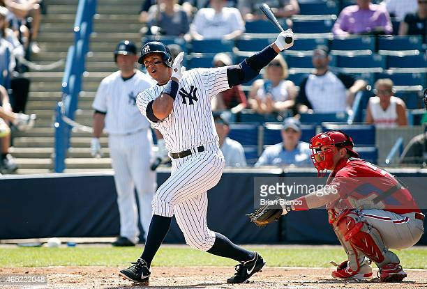 Designated hitter Alex Rodriguez of the New York Yankees follows through as he hits a single to left field in front of catcher Tommy Joseph of the...