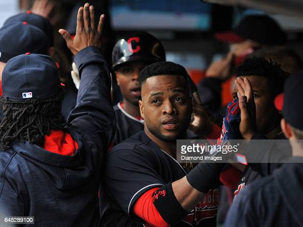 Designated hitter Carlos Santana of the Cleveland Indians high fives teammates in the dugout after scoring a run in the second inning of a game...