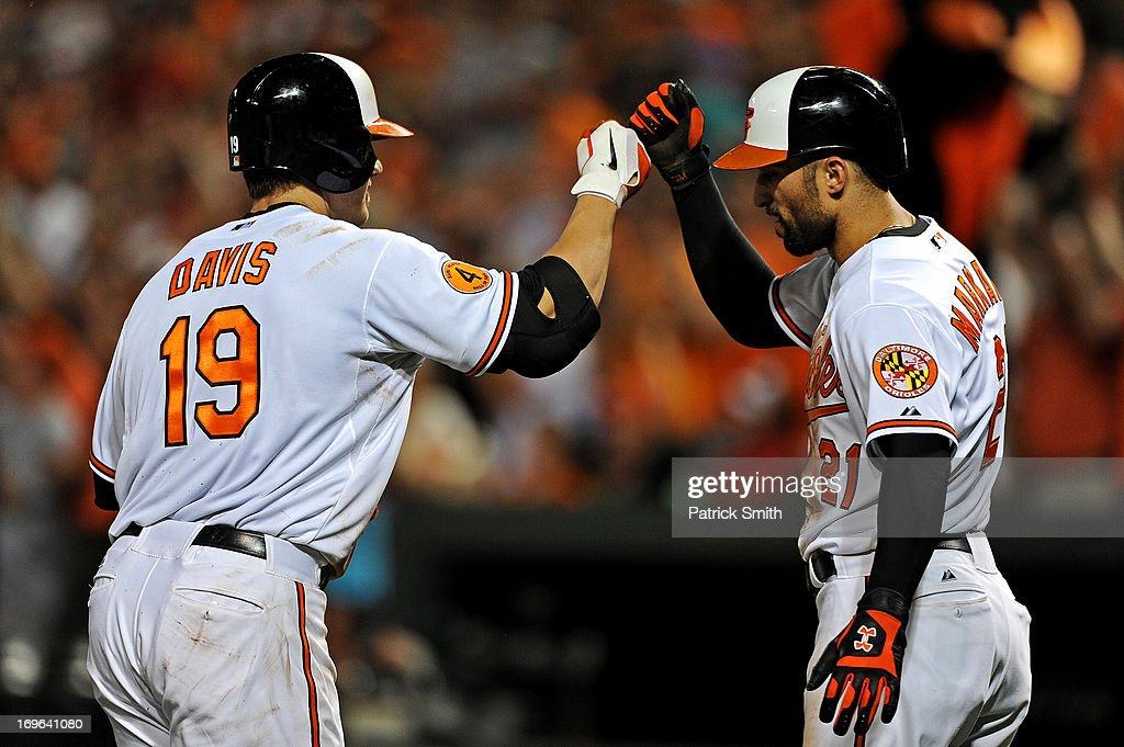 Designated hitter Chris Davis #19 of the Baltimore Orioles high-fives teammate <a gi-track='captionPersonalityLinkClicked' href=/galleries/search?phrase=Nick+Markakis&family=editorial&specificpeople=614708 ng-click='$event.stopPropagation()'>Nick Markakis</a> #21after hitting a two-run home run in the seventh inning against the Washington Nationals during an interleague game at Oriole Park at Camden Yards on May 29, 2013 in Baltimore, Maryland. The Baltimore Orioles won, 9-6.