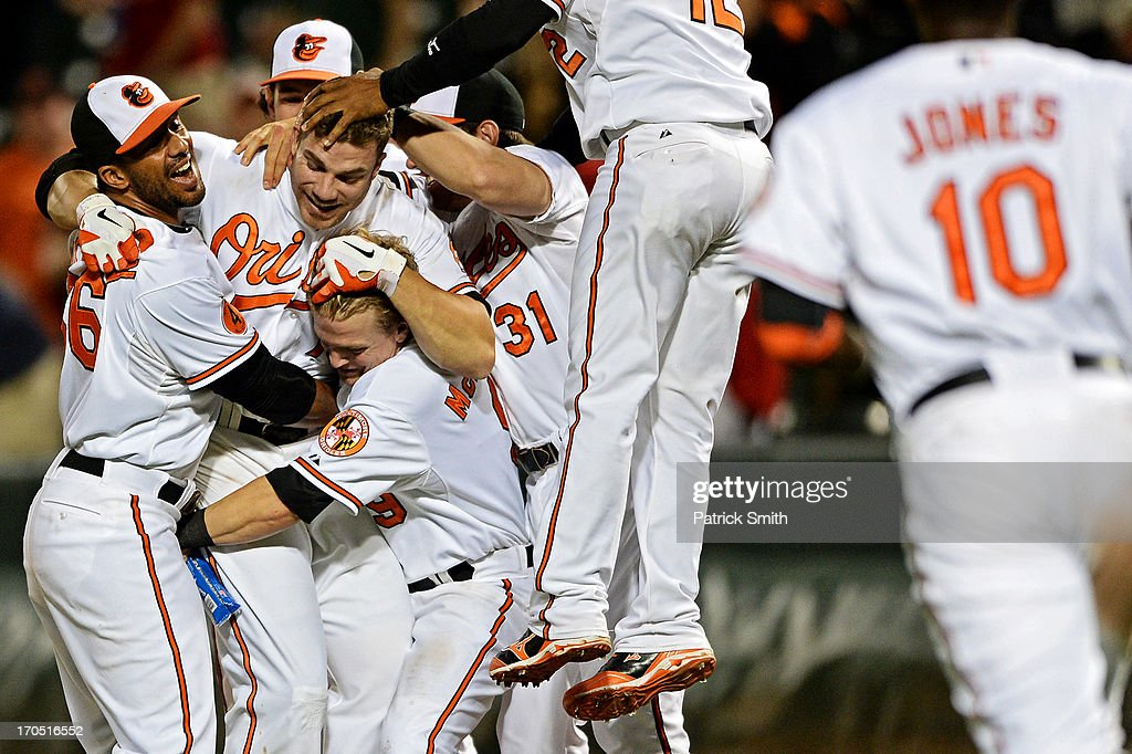 Designated hitter Chris Davis #19 of the Baltimore Orioles is mobbed by teammates after hitting the game-winning RBI against the Boston Red Sox in the 13th-inning at Oriole Park at Camden Yards on June 13, 2013 in Baltimore, Maryland. The Baltimore Orioles won, 5-4, in 13-innings.