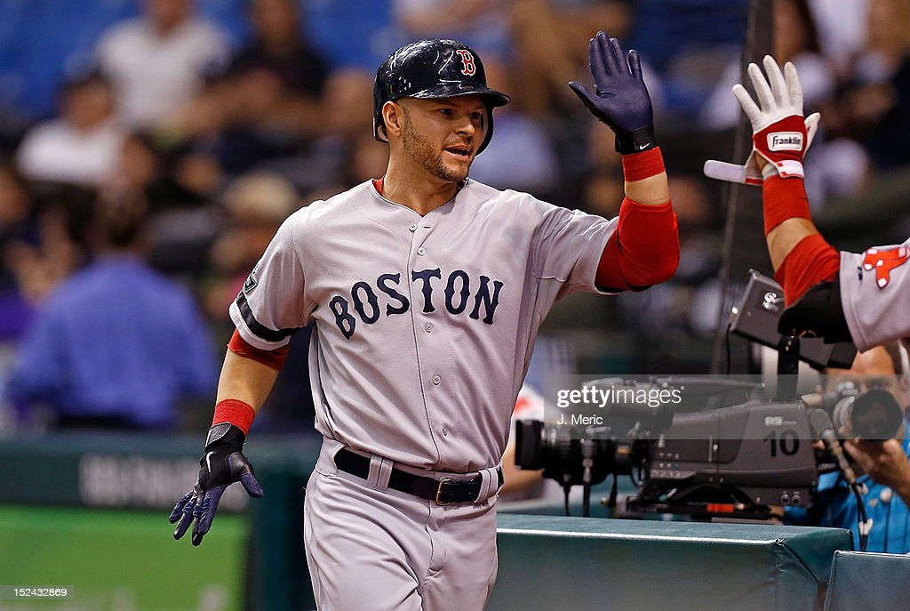 Designated hitter <a gi-track='captionPersonalityLinkClicked' href=/galleries/search?phrase=Cody+Ross&family=editorial&specificpeople=545810 ng-click='$event.stopPropagation()'>Cody Ross</a> #7 of the Boston Red Sox is congratulated after scoring against the Tampa Bay Rays during the game at Tropicana Field on September 20, 2012 in St. Petersburg, Florida.