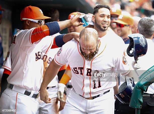 Designated hitter Evan Gattis of the Houston Astros is doused with water by Luis Valbuena after hitting a three run home run in the first inning...