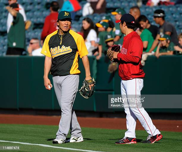 Designated hitter Hideki Matsui of the Oakland Athletics his and reliever Hisanori Takahashi of the Los Angeles Angels of Anaheim during talks during...