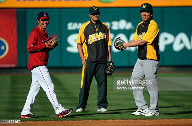 Designated hitter Hideki Matsui of the Oakland Athletics his interpreter Roger Kahlon and reliever Hisanori Takahashi of the Los Angeles Angels of...