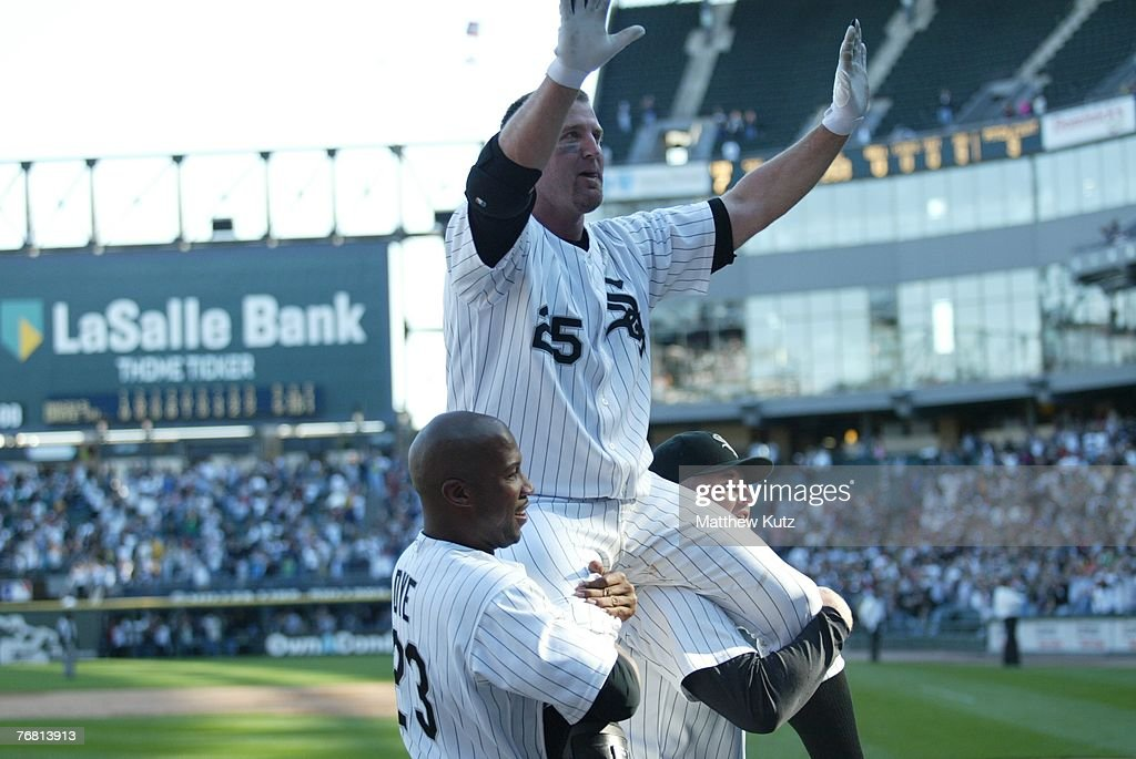 Designated hitter Jim Thome of the Chicago White Sox celebrates with teammates while being carried by teammates pitcher Bobby Jenks and right fielder...